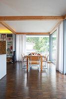 Blick auf Esstisch in offenem Wohnbereich mit rundum Verglasung
