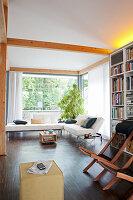 Liegestühle vor Regalwand und Designersofa in offenem Wohnraum
