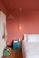 Bett mit weißer Bettwäsche im Schlafzimmer mit lachsfarbenen Wänden