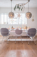 Spherical silver lamps above festively set dining table and grey chairs