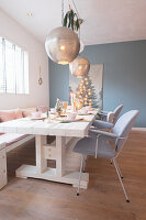 Spherical silver lamps above festively set dining table