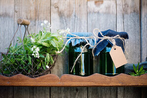 Jars of home-made sweet woodruff jelly on wooden shelf