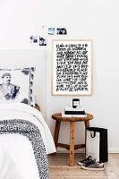 Schriftbild über einem alten Hocker als Nachttisch neben dem Bett