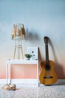 Gitarre und Tisch an der Wand mit Farbverlauf in Rosa und Blau