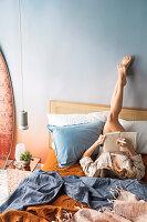 Frau liegt auf dem Bett und schreibt in ein Buch