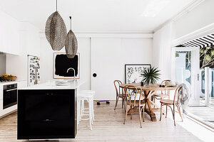 Offene Wohnküche in Schwarz und Weiß mit Holztisch und Terrasse