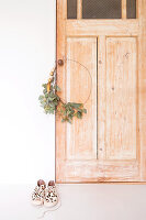 Minimalist wreath on wire ring hung on wooden door