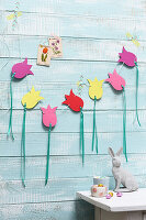 Garland of paper tulips on pale blue board wall
