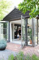 Blick durch geöffnete Terrassentüren in Wohnbereich, Mutter mit Kind vor schwarzer Pinnwand