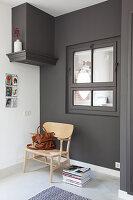 Stuhl und Bücherstapel vor dunkler Wand mit Innenfenster