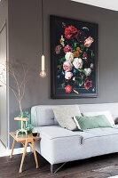 Grey sofa with scatter cushions, side table, pendant lamp and floral painting