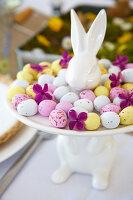 Bunte Zuckereier auf weißer Platte mit Osterhase
