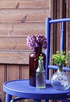 Braune und weiße Flaschen und Glasvase mit Blumen auf blauem Stuhl
