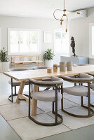 Elegant upholstered chairs around wooden table in grey dining room