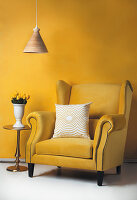 Yellow wing-back chair with pale scatter cushion, yellow tulips on side table and pendant lamp in front of yellow wall