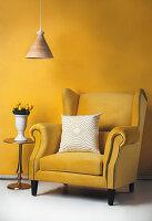 Gelber Ohrensessel mit Kissen, Beistelltisch mit gelben Tulpen und Pendelleuchte vor gelber Wand