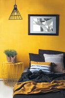 Bett und Nachttisch aus Metall vor gelber Wand