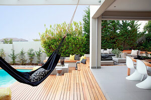Hammock between swimming pool and roofed terrace