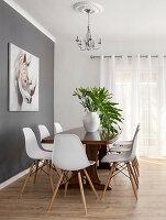 Weiße Designerstühle um einen Holztisch vor grauer Wand