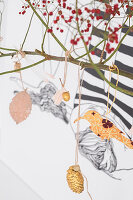 Branch decorated with golden fir cone and acorn and paper bird