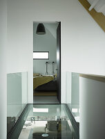 Glass walkway with glass balustrade leading to bedroom in architect-designed house