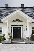 White country house with porch and black roof