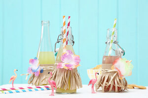 Bottles of lemonade decorated with paper strips and fabric flowers