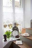 Weiße Tulpen und Flohmarktartikel am Fenster neben der Treppe