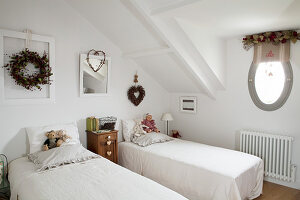 Old teddy bears and doll on twin beds in vintage-style attic bedroom