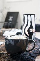 Heisses Getränk mit Marshmallows in schwarzer Tasse, im Hintergrund DIY-Windlicht
