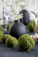 Handmade moss balls on table set with black tablecloth