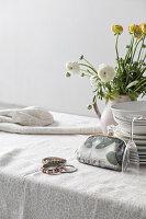 Vase of ranunculus, stacked plates, Champagne glass, make-up bag and bracelets on table