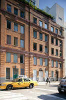 Yellow taxi outside typical American brick façade