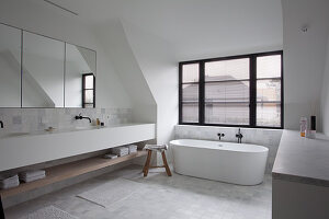 Großzügiges Badezimmer mit frei stehender Badewanne vor Fenster und Doppelwaschtisch