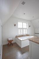 Badewanne mit Marmorablage vor Fenster, daneben Holzhocker in weißem Badezimmer