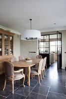 Holztisch und Polsterstühle vor Geschirrschrank in elegantem Esszimmer mit Naturstienfliesen