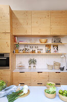 Wooden cupboards and open shelves in simple kitchen