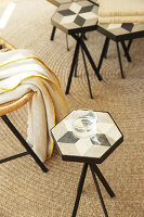 Glass of water on side table with top made from hexagonal cement tile