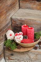 Gehäkelte Weihnachtsdekoration und rote Kerzen auf rustikaler Holztreppe