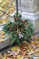 Grave arrangement of conifer twigs, Gaultheria berries, pine cones and silver ragweed