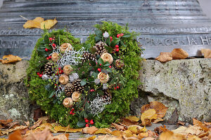 Moss love-heart decorated with Gaultheria berries, poppy seedheads and silver ragweed