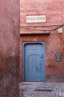 Brick façade and blue front door of the Hotel Ryad Dyor (Marrakesh, Morocco)