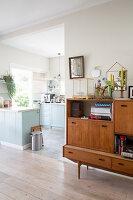 Retro sideboard in living room next to open doorway leading into kitchen