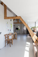 Console table and chair in open-plan attic room with white floor