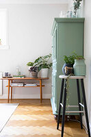 Plants on bar stools and console table flanking green cabinet