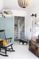 Rocking chair, dolls' pram and grey wardrobe in white nursery