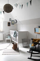 White cot and rocking chair in nursery with white wooden floor
