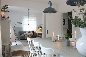 White wooden table and wooden chairs in open-plan interior