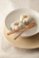 Fresh garlic and cutlery in bowl