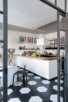 Kitchen counter and dining area on black-and-white tiled floor seen through interior partition